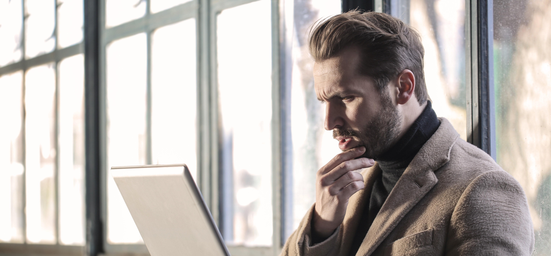man-wearing-brown-jacket-and-using-grey-laptop